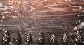 Horizontal brown wood background with golden cones at the bottom. Holiday space for winter, xmas, New Year and Christmas holidays. Effect of light blips and Stock Photography
