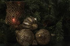 Horizontal Christmas display with gold wooden ball ornaments. Christmas display with glass mosaic candle holder and greenery in the background and golden wood Stock Images