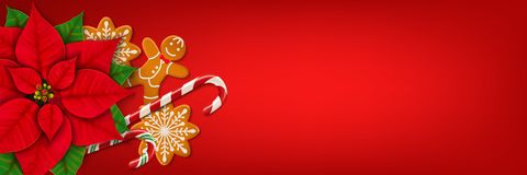 Christmas horizontal web banner on red background. Horizontal Christmas web banner. Poinsettia, gingerbread cookies, candy canes and place for your text on the Royalty Free Stock Image