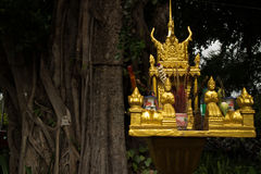 Horizontal close up of a gold spirit house and large tree in Sou Royalty Free Stock Images