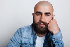 A horizontal close-up of handsome bald man having charming dark eyes, thick black eyebrows and beard wearing jean shirt holding hi. S hand on chin while thinking royalty free stock photography