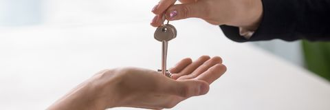 Closeup hands real estate agent giving keys to home owner stock images