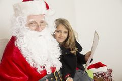 Santa Claus with a girl. This horizontal close up portrait of Santa and a girl that holding a letter to Santa Claus. they are looking directly to the camera and Stock Photos