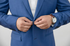 Horizontal close-up shot of young Caucasian male closing the button of his jacket Stock Images