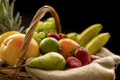 Horizontal Closeup detail on a basket full of fruit on a dark background. Horizontal closeup detail on a basket full of fruit (banana, strawberry, pineapple Stock Photo