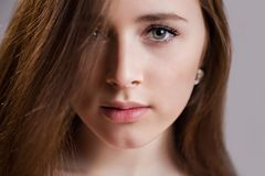 Horizontal closeup portrait of a beautiful young woman with clean skin, long eyelashes and natural beauty, fresh face. Green eyes, charming girl`s look into stock photo