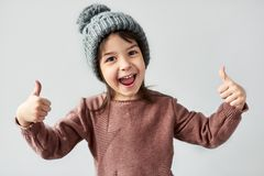Horizontal closeup portrait of happy smiling little girl in the winter warm gray hat, wearing sweater and showing thumbs up, stock image