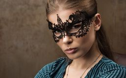 Horizontal closeup portrait of young beautiful woman in mask on her eyes. A delicate lace mask. Professional make-up. Green dress Stock Photos
