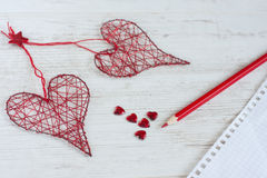 Love letter. Horizontal composition of bright red pensil, glass mimi hearts and two handmade hearts royalty free stock photos