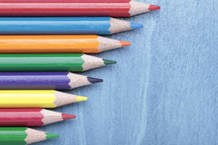 Horizontal composition of some crayons. Some crayons aligned on a horizontal composition on blue background Stock Images