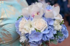 Caucasian young bridesmaid or female guest wearing a blue dress with silver details and holding a beautiful mixed bouquet. Horizontal cropped detail shot of Stock Photo