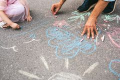 Horizontal cropped image of little girl and dad drawing with colorful chalks on the sidewalk. Handsome male play together with his. Cute kid preschooler outdoor royalty free stock photos