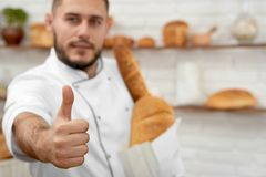 Young man working at his bakery. Horizontal cropped shot of a handsome male baker showing thumbs up posing proudly at his bakery store holding paper bag full of Royalty Free Stock Images