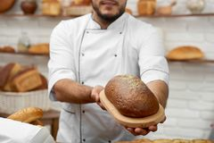 Young man working at his bakery. Horizontal cropped shot of a professional baker holding out loaf of delisious fresh bread posing at his store selling pastry Stock Photography