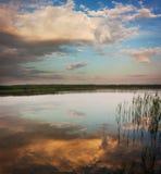 Horizontal d'été avec le lac calme au coucher du soleil Photos stock