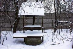 Horizontal de l'hiver Vieux campagne puits d'eau avec la poulie et le seau Région Ukraine de Kiev Photos libres de droits