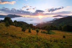 Horizontal de montagne Lever de soleil dans les nuages Brouillard dense avec la lumière molle gentille Sur la pelouse l'herbe et  Image libre de droits
