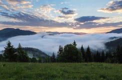 Horizontal de montagne Lever de soleil dans les nuages Brouillard dense avec la lumière molle gentille Sur la pelouse l'herbe et  Images stock