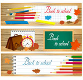Horizontal de nuevo a banderas de escuela con las herramientas de la escuela y las hojas de otoño en la superficie de madera Fotos de archivo