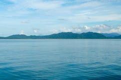 Horizontal do Seascape que inclui Forest Mountain, o céu azul e a onda da água Imagem de Stock