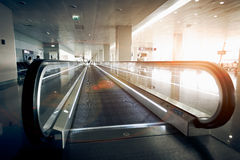Horizontal escalator at modern airport terminal at sun light. Long horizontal escalator at modern airport terminal at sun light Royalty Free Stock Image