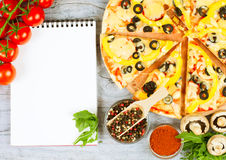 Horizontal food banner with cherry tomatoes, cutted pizza, spice and notebook on wooden background. Empty space for text. Kitchen background. Top view. Concept Royalty Free Stock Photos