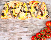 Horizontal food banner with pieces of homemade pizza red cherry tomatoes on wooden background. Empty space for text. Kitchen background. Top view. Concept for Royalty Free Stock Photos