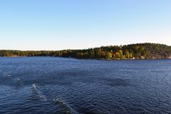 Autumn yellow-green forest and blue sea from the ferry deck on the way to Stockholm stock images