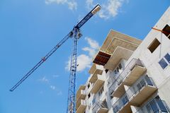Building under construction, construction crane against the sky stock image