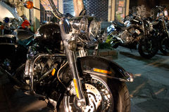Horizontal Front View of Fat Cruiser Motorcycle with Chrome Fork. At Night; other bikes can be seen indistinctly in the background Royalty Free Stock Images