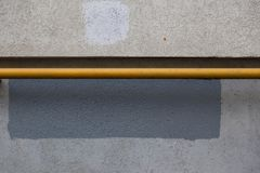 A horizontal gas pipe painted with yellow paint next to the building wall. Texture of concrete. Rectangle of gray paint. Over the spot of obscene graffiti Royalty Free Stock Photography