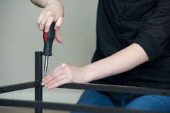 Horizontal of hands screwing together metal furniture, angled left. Horizontal of hands screwing together furniture, angled left Royalty Free Stock Images