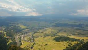 Horizontal high panorama to mountains, fields, river, village, sky with cloud. Horizontal Panorama with View from the Height to Mountains, Fields, River, Village stock footage