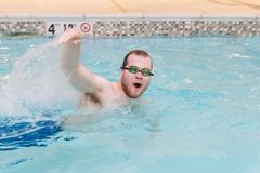 Young adult male swimming in indoor pool. Horizontal image of a caucasian young adult male wearing goggles swimming fast across an indoor pool Royalty Free Stock Image