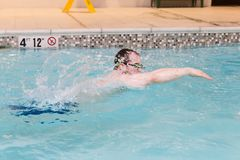 Young caucasian male in motion swimming in pool. Horizontal image of a caucasian young adult  male  wearing goggles swimming with great moyion in an indoor pool Stock Photo