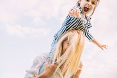 Horizontal image of happy little daughter on a piggy back ride with her smiling mother on sky background. Loving woman and her. Horizontal image of happy little royalty free stock photography