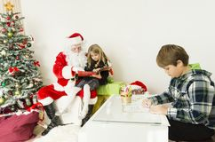 Santa claus with kids reading a book. This horizontal image has a scene with Santa Claus and kids. on the left side of this image is a Christmas tree with a Star Royalty Free Stock Images