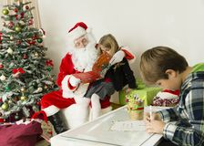 Santa Claus with kids. In this horizontal image in the left side is a Christmas tree with a big bag of gifts on the bottom. on the middle of this image are a Royalty Free Stock Photos