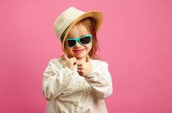 Horizontal image of little girl in straw hat and sunglasses, shows a thumb up, glances at you, stands on isolated pink. royalty free stock photo