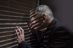 Mature man looking out of a window with blinds casting shadows. Horizontal image of a mature man looking out of a window with blinds casting shadows stock photography