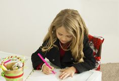Girl is drawing a letter to Santa Stock Images