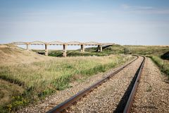 Railroad track running around a curve and under a big concrete bridge. Horizontal image of a railroad track curving and running under an old concrete arched Stock Image