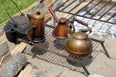 Horizontal image of several cast iron and copper kettles on open fire pit. Several cast iron and copper kettles set on grates by open fire pits at cookout Royalty Free Stock Photo