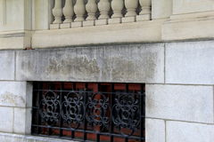 Horizontal image of stone building with carved railing and wrought iron enclosures. Exterior of stone building shows craftsmanship of carved railings and black royalty free stock image
