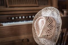Straw hat hanging on a chair post next to an organ. Horizontal image of a straw cowboy hat hanging on a chair next to the church organ Royalty Free Stock Photography