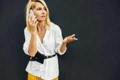 Horizontal image of surprised business woman standing next to gray wall while talking on smart phone. Unhappy student female royalty free stock photo
