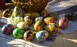 Colorful Easter eggs beside a basket on embroidered napkin royalty free stock photos