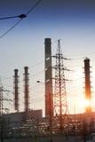 Horizontal industriel Coucher du soleil au-dessus de la ligne électrique et des tuyaux de l'usine de production combinée de chale Photos stock