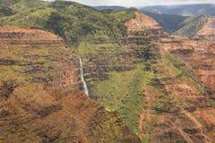 Horizontal layers in the rocks lead to Waimea Falls Stock Photo