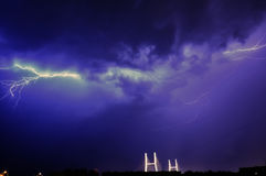 Horizontal lightning. Illuminating the night cloudy sky in the background two pylons of the bridge Royalty Free Stock Images